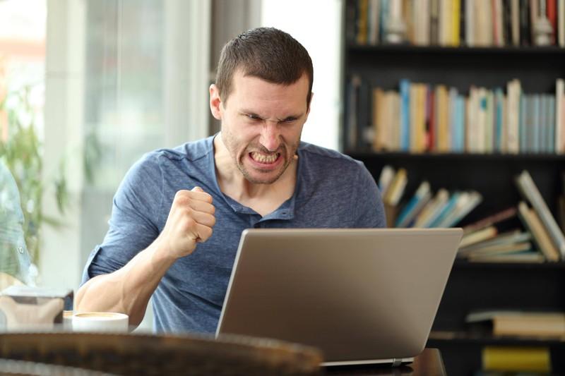 Mann sitzt wütend am Laptop