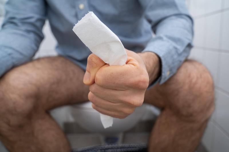 Ein Mann sitzt auf der Toilette und hat Schmerzen