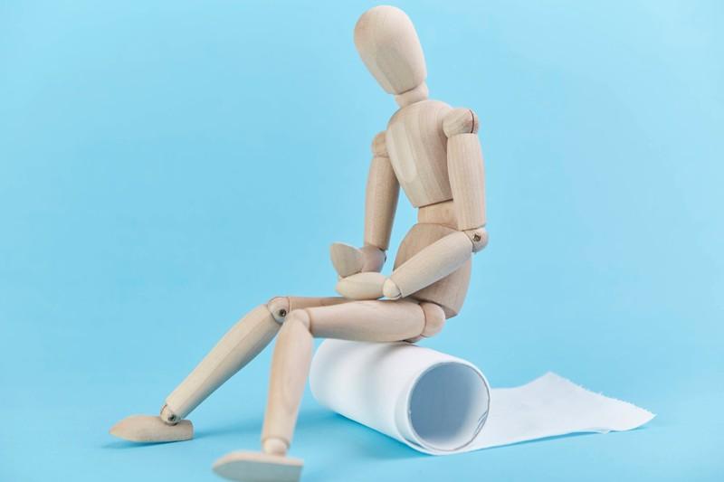 Eine Holzfigur sitzt auf Toilettenpapier, ein Symbolbild für Stuhlgang